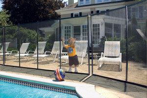 Small kid by fence of pool